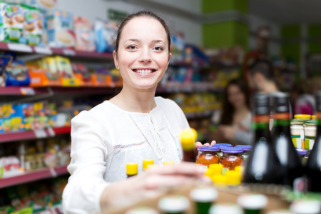 canned goods: Happy woman standing near shelves with canned goods at shop Stock Photo