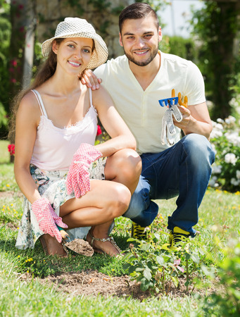 floriculturist: Smiling family with gardening tool working in their garden Stock Photo