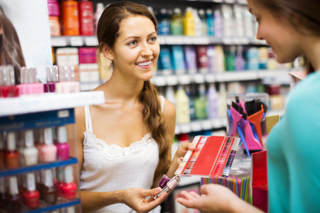store clerk: Store clerk serving purchaser with nail polish