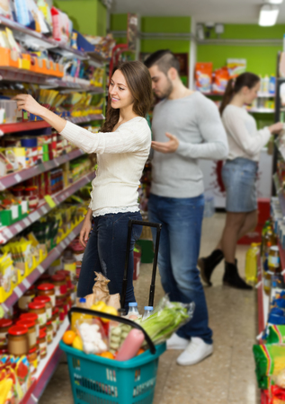 canned goods: european customers standing near shelves with canned goods at shop