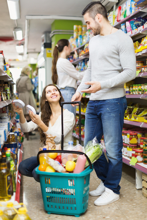 canned goods: Positive adults people standing near shelves with canned goods at shop
