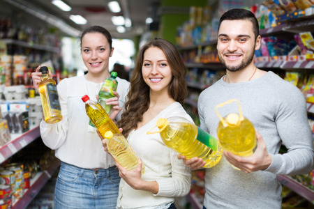 unrefined: Positive adults holding seed-oil in plastic packing at shop. Focus on girl
