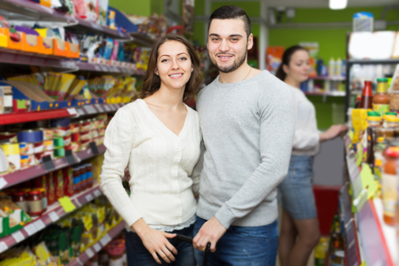 canned goods: smiling european customers standing near shelves with canned goods at shop