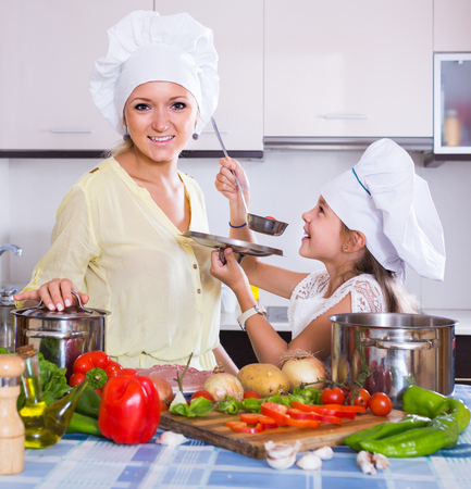 vegeterian: smiling american mom and little daughter cooking vegeterian dish indoors