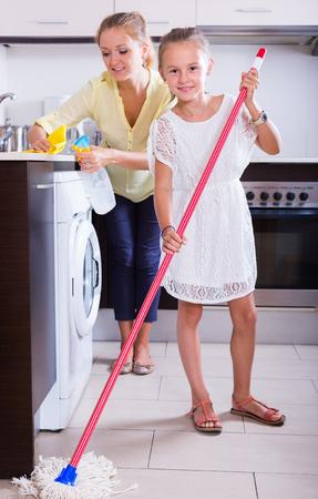 limpieza del hogar: Ni�a sonriente ayudando gozosa madre a limpiar en la cocina en el hogar