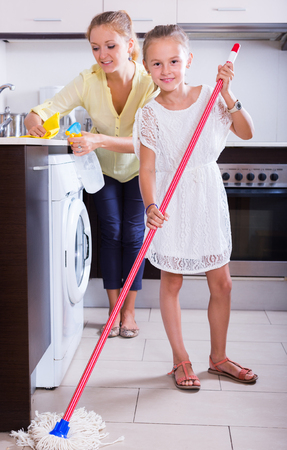 spanish house: Smiling little girl helping joyful mother to clean in the kitchen at home Stock Photo