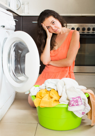 unsatisfactory: Sad housewife with clothes near washing machine at home Stock Photo
