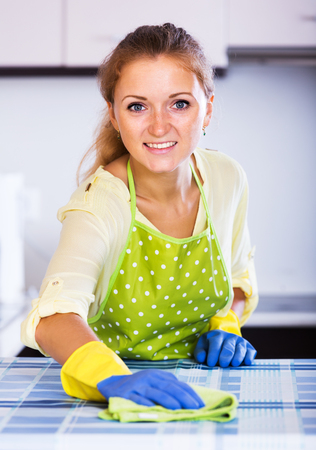 dusting: Young woman dusting kitchen top in home interior