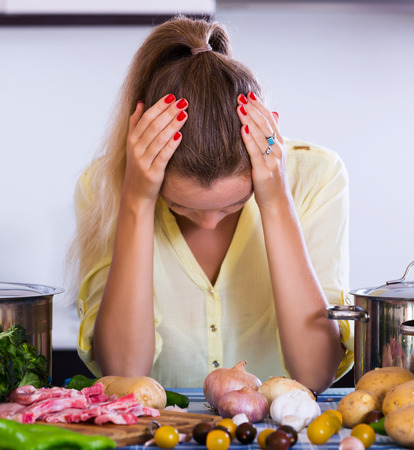caras: Unhappy girl looking at dinner ingredients with sad face