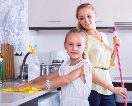 diligente: La ni�a alegre diligente ayudar a la madre sonriente alegre a limpiar en la cocina en el hogar Foto de archivo