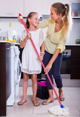 cleanup: Little girl helping smiling young woman  doing regular cleanup at kitchen