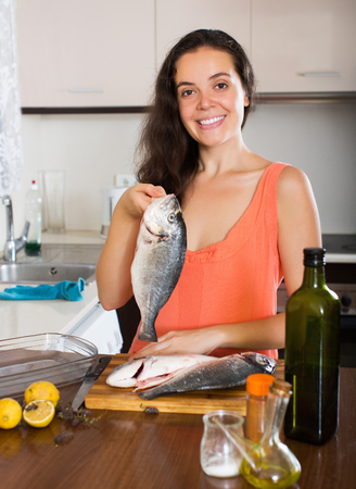 gilthead bream: Happy young woman holding raw fish at kitchen