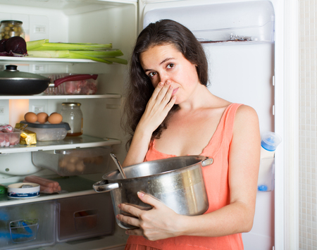 frowy: Girl holding her nose because of bad smell from pan near refrigerator  at home
