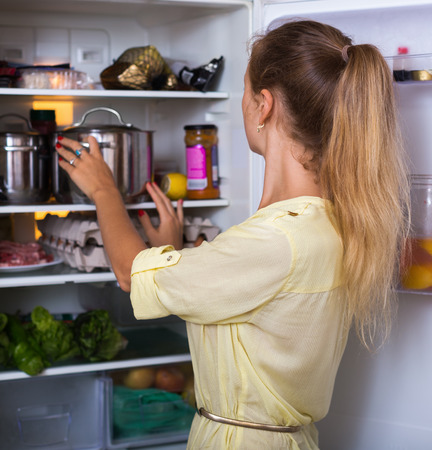 fridge: Happy housewife arranging products on fridge shelves