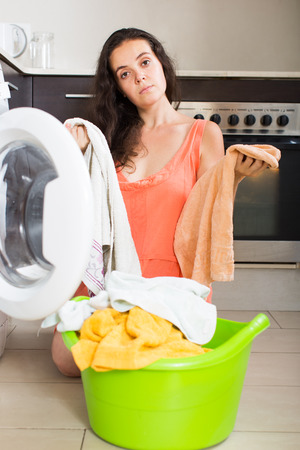 unsound: Unhappy young housewife with clothes near washing machine at home