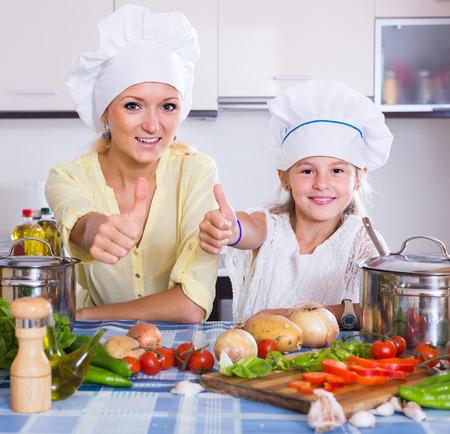 vegeterian: happy european mom and little daughter cooking vegeterian dish indoors Stock Photo