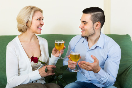 mismatch: Smiling mature woman with young boyfriend drinking wine indoors