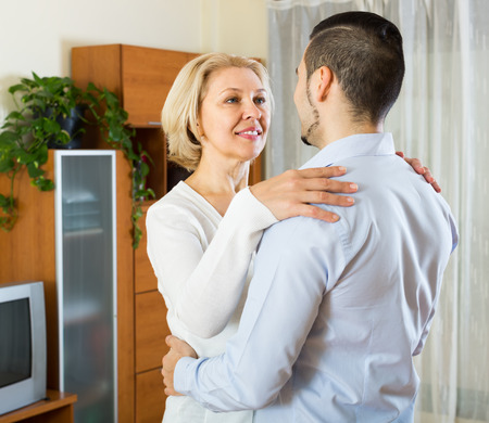 gigolo: Young smiling man and senior woman slowly dancing indoor