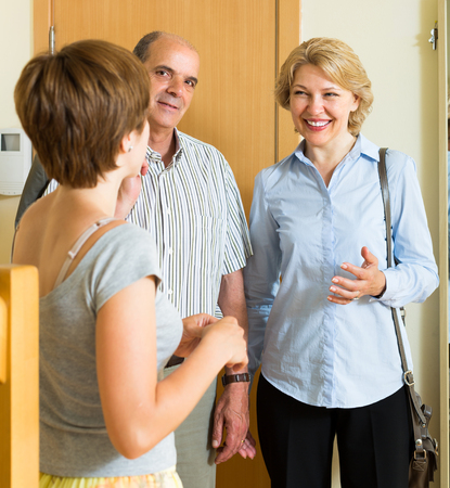 mature old generation: Young woman meeting smiling senior mature friends at the door