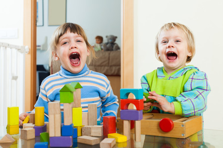 emotional: Emotional sibling playing in toy blocks in home interior