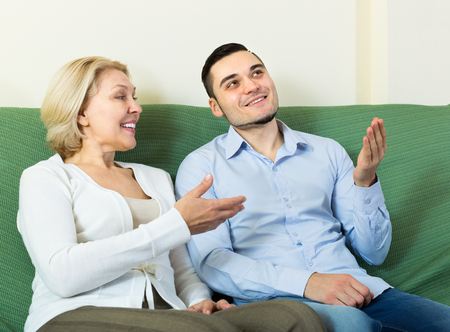 mismatch: Handsome man and elderly woman having pleasant conversation at home Stock Photo