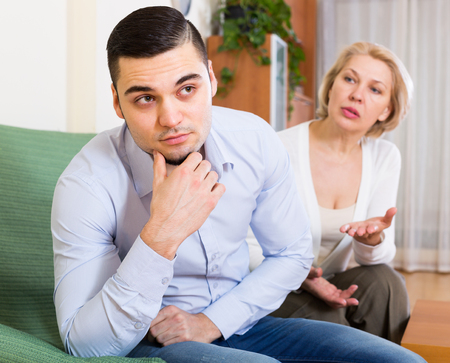 mismatch: Serious conflict of aged woman and her young boyfriend Stock Photo