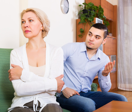 offended: Sad young man explaining something to offended elderly woman
