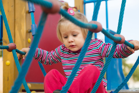 adroitness: girl at action-oriented playground in summer Stock Photo
