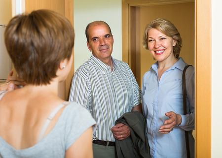 threshold: Positive adult daughter greeting elderly parents at threshold