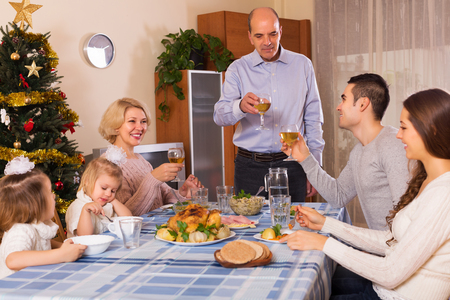 three generations of women: United smiling family at festive table near Christmas tree Stock Photo