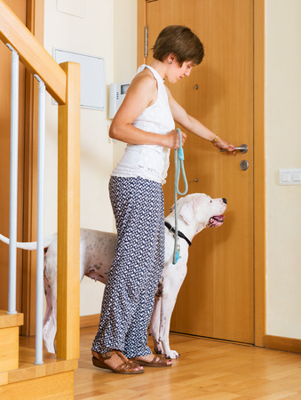 staying: Young woman with white big dog on leash staying at door
