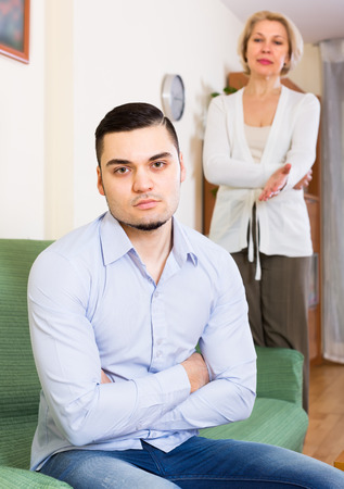 mismatch: Domestic conflict between adult son and senior mature mother Stock Photo