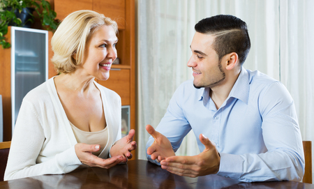 Smiling young son talking with senior mother at her place Stock Photo