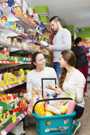tinned: Cheerful adults choosing tinned food at supermarket