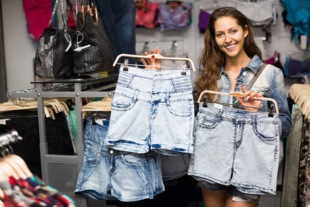 spanish girl: Young smiling spanish girl buying shorts in commercial centre Stock Photo