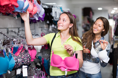 brassiere: Young attractive woman buying the brassiere at clothing store