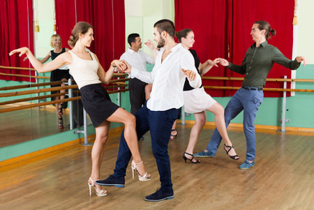 merry dancers: Tree happy spanish couples dancing rock-and-roll in dancing-class Stock Photo
