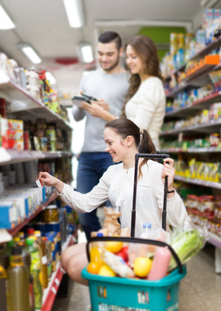 canned goods: happy american customers standing near shelves with canned goods at shop Stock Photo