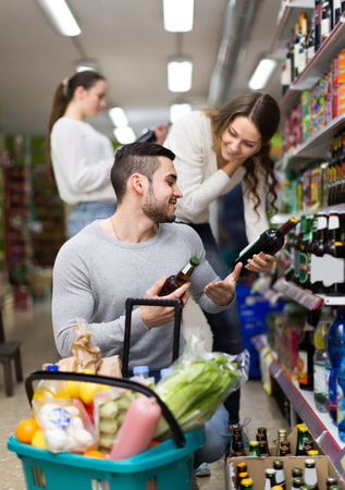 people buying: Positive people buying beverages for dinner indoors