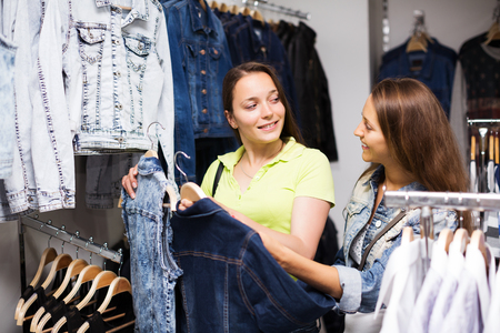 Two young smiling girls buying jacket in clothing store Stock Photo