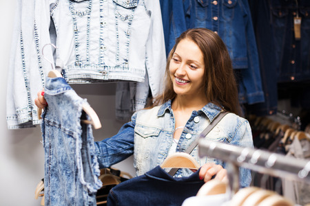 clothing store: Young smiling girl buying vest in clothing store