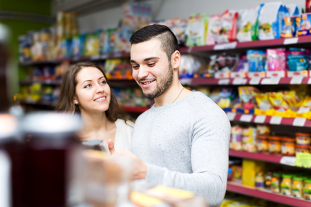 canned goods: Portrait smiling couple standing near shelves with canned goods at shop. Focus on the man Stock Photo