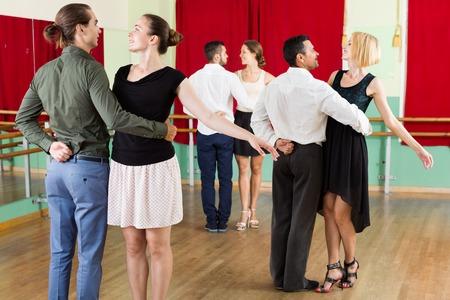 dance steps: Tree  beautiful  smiling couples dancing waltz in dancing-class