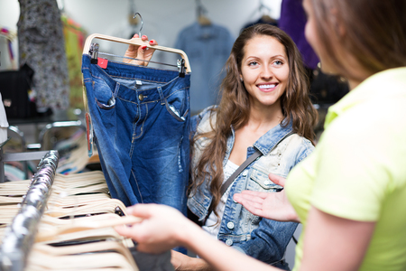 denim trousers: Woman shopper choosing denim trousers at shop