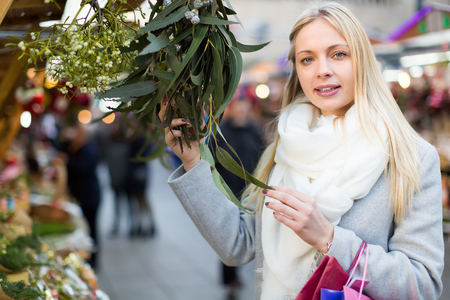 overspending: Young woman buying floral decorations at a Xmas fair