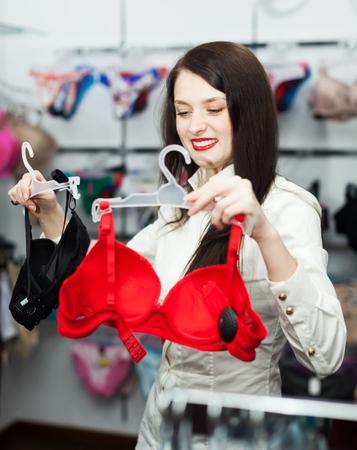 clothing store: Ordinary woman choosing bra at clothing store