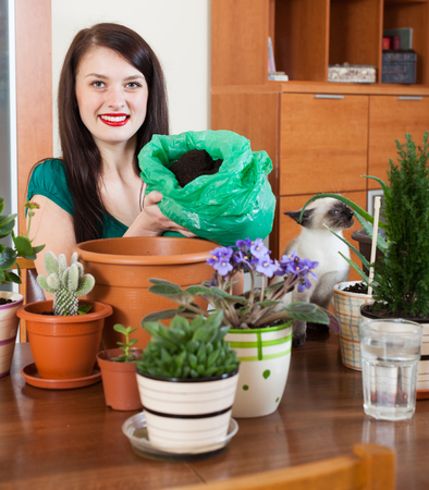 replant: girl transplanting potted flowers at home