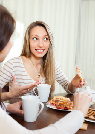 blabber: two happy girls  drinking tea and gossiping in home