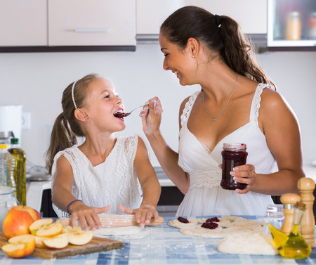 25s: Portrait of young woman and child cooking sweet pies Stock Photo