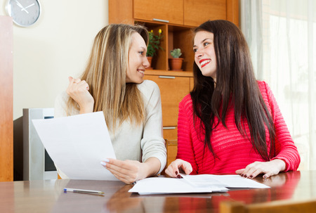 home office interior: Happy women with  documents  in home or office interior